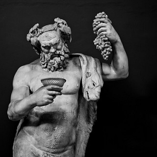 """Derek Key,  """"Dionysus - Statue at the Vatican"""" , 18 April 2013. A picture of a statue of Dionysus. He is holding a bunch of grapes in his left hand, and a bowl in his right. An animal pelt hangs over his left shoulder."""