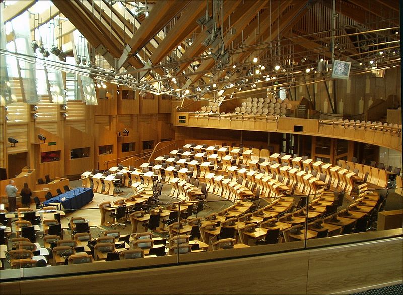 """Pschemp, """" Debating chamber in Scottish Parliament building """", 31 May 2006. A picture of a debating chamber of the Scottish Parliament building during the day."""
