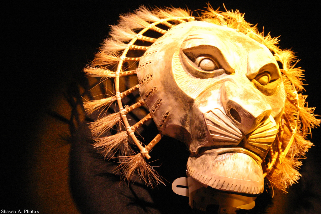 A mask of the lion king, depicting a fierce three dimensional lion face that is carved onto wood and attached to short straws to showcase its mane.