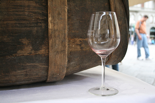 empty wine glass in front of barrel