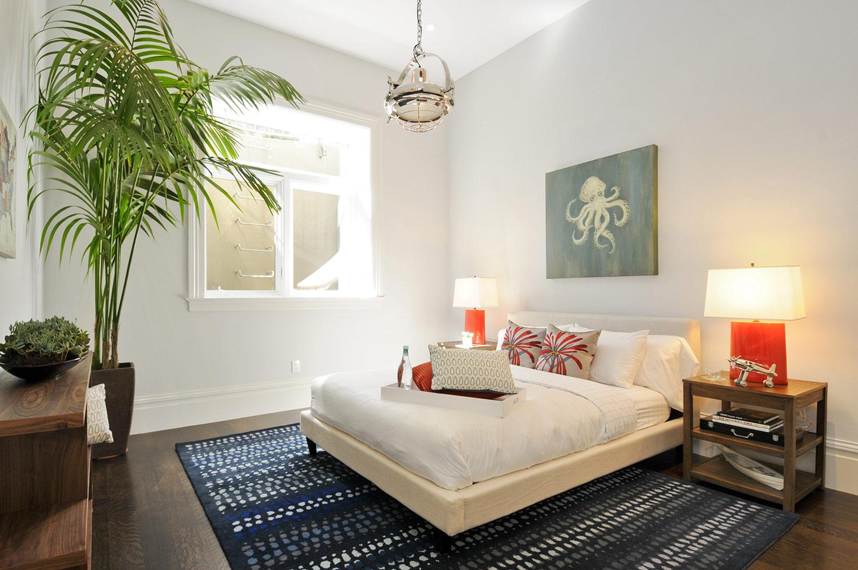 beachy bedroom, blue rug, fabric bedframe, bedside table lamps, indoor plants, artwork