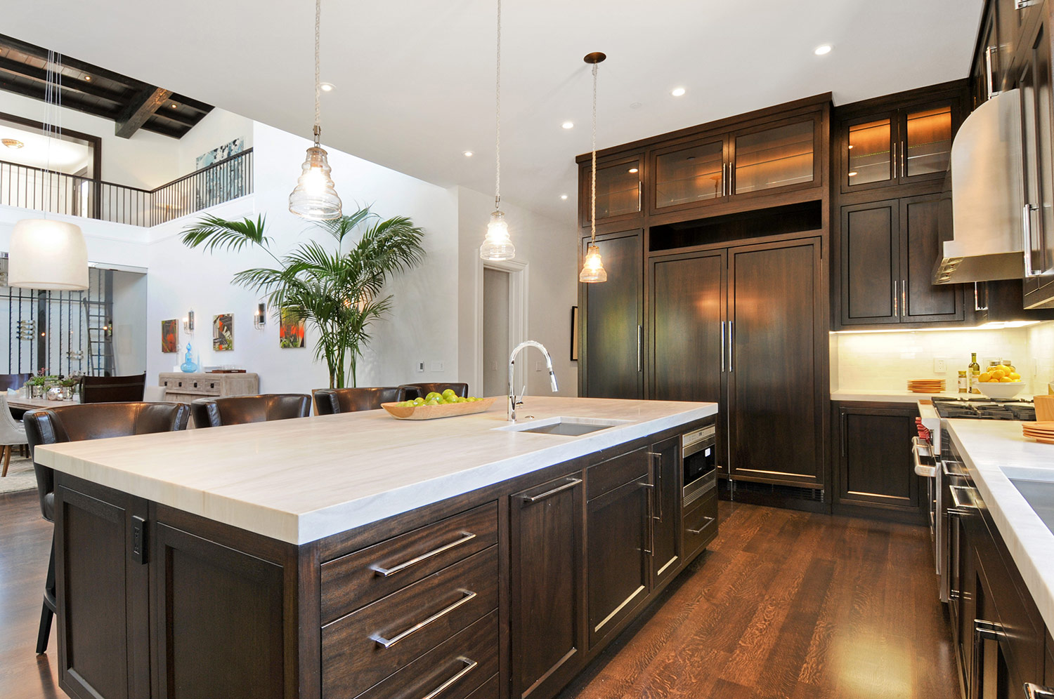 ktichen, cabinetry, hardwood floors, wolf stove, marble counters, barstools, kitchen pendant, stainless steel range, high ceilings