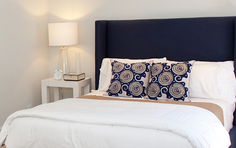 modern bedroom, bed, throw pillows, bedside table, bedside lamp