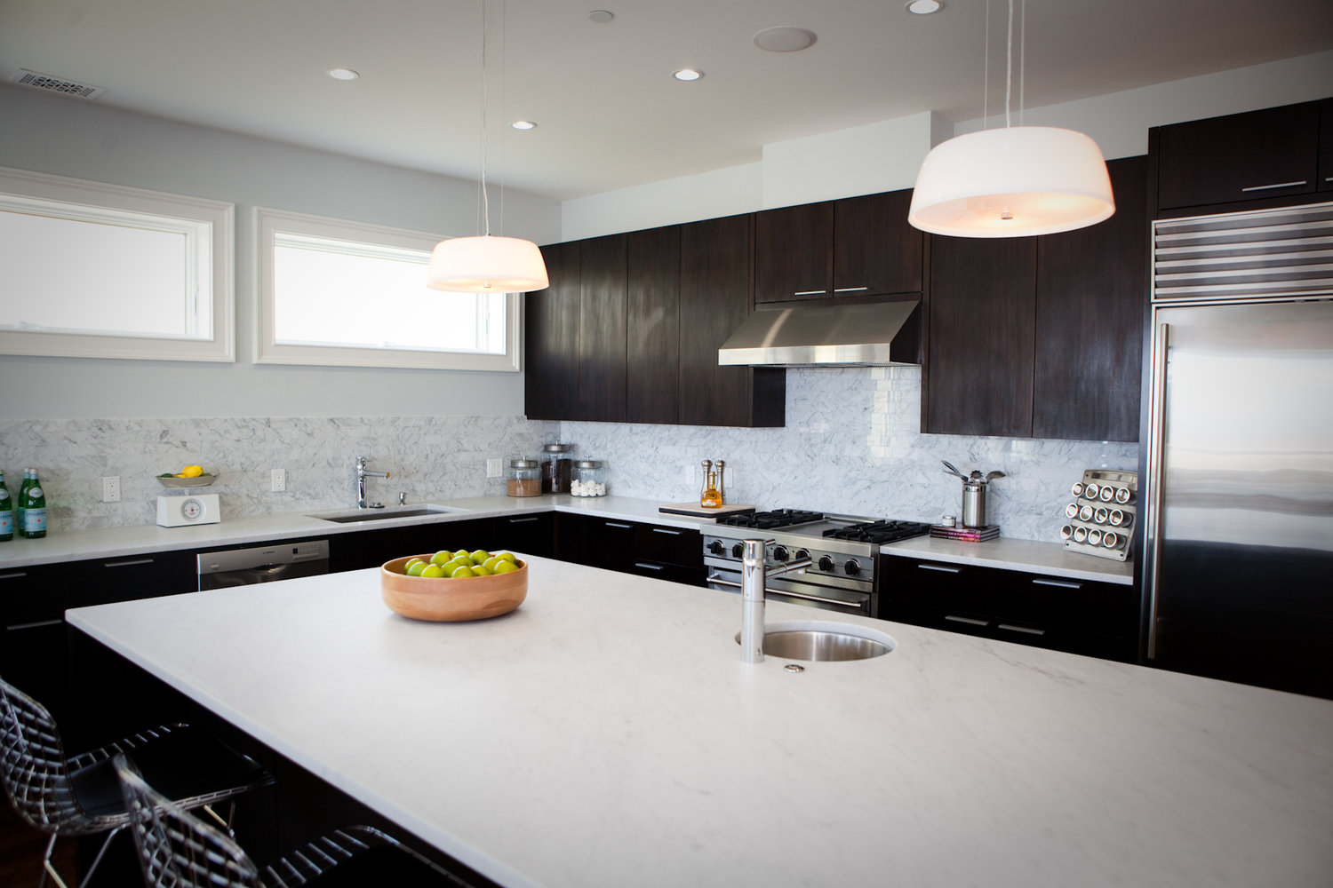 kitchen, barstools, kitchen island, marble counters, tile backsplash, stainless steel appliances, modern kitchen, dark cabinets, polished chrome faucet, kitchen sink, prep sink