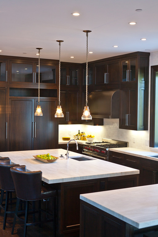 dark cabinetry, stainless steel, marble counters, barstools, kitchen pendants, prep sink, polished chrome faucet