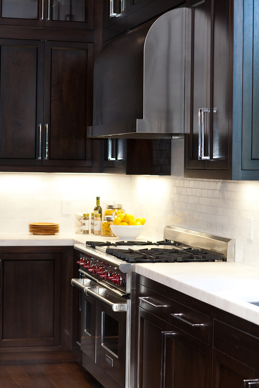 dark cabinetry, stainless steel, marble counters, barstools, kitchen pendants, prep sink, polished chrome faucet, wolf range