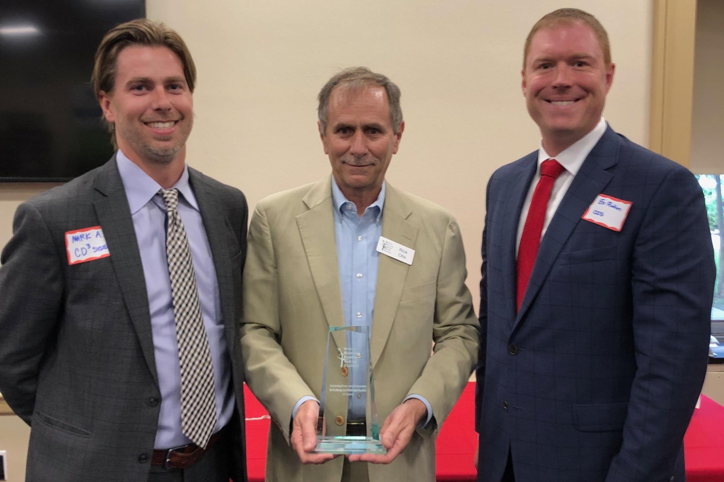 Mark Apfelbacher & Dr. Edgar Rudberg accept award from Rick Otis, President of RRISC