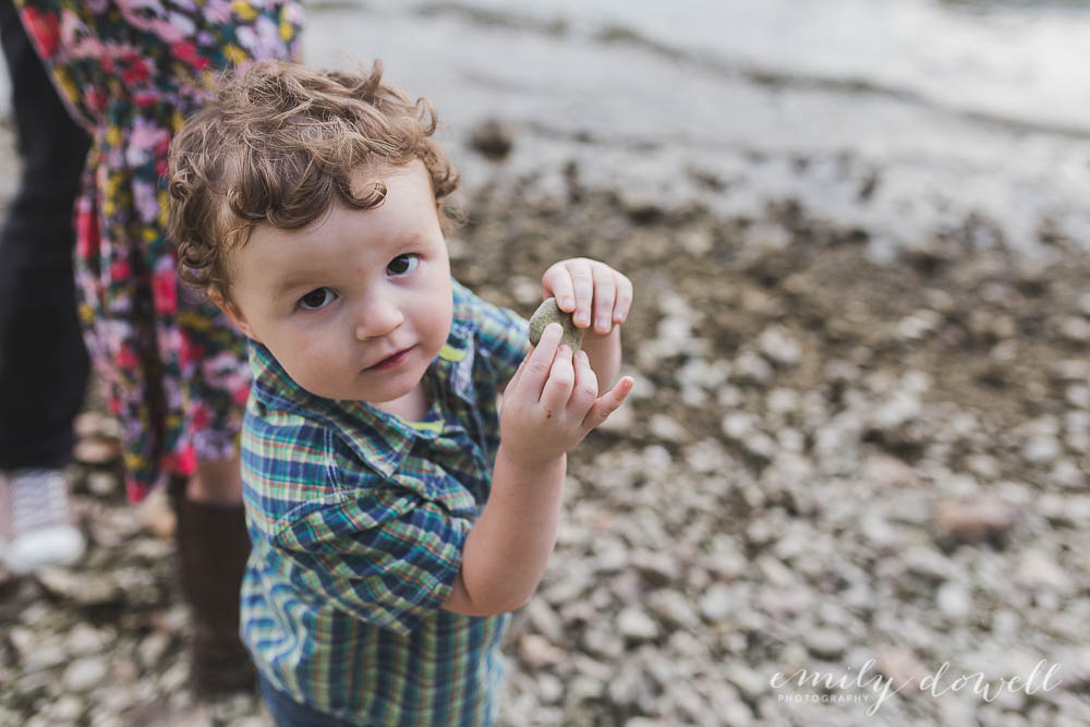 portrait of toddler holding a rock on a shoreline