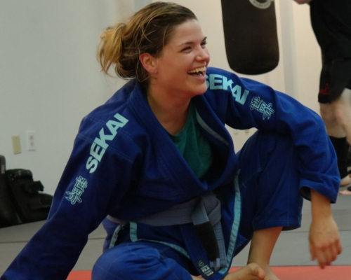 Sydney Lewis - Sydney Lewis always shows exemplary skills and character on and off the mats. Whether training in Brazilian Jiu-jitsu, helping kids in our after school program or teaching the Women's Kick Boxing, Sydney excels in everything she does. She has been training in the martial arts since 2009, earning her Black Belt in Moo Duk Kwan in 2014. She is currently a Brown belt Brazilian Jiu-jitsu under Professor Jonathan Uzcategui. and has become a testimony of our motto