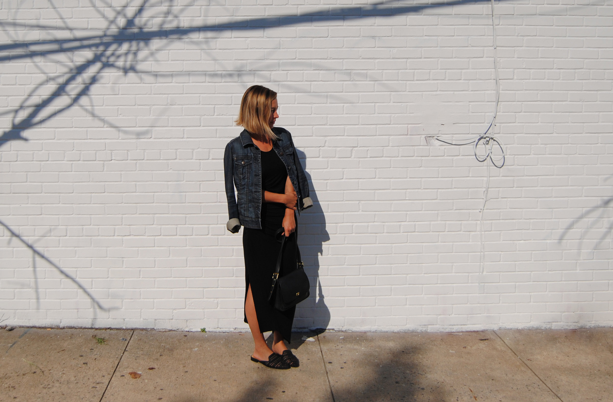 leanne luce in neural network-inspired outfit, black asymmetrical jersey dress from target, denim jacket, black coach bag, and black woven mules from target.