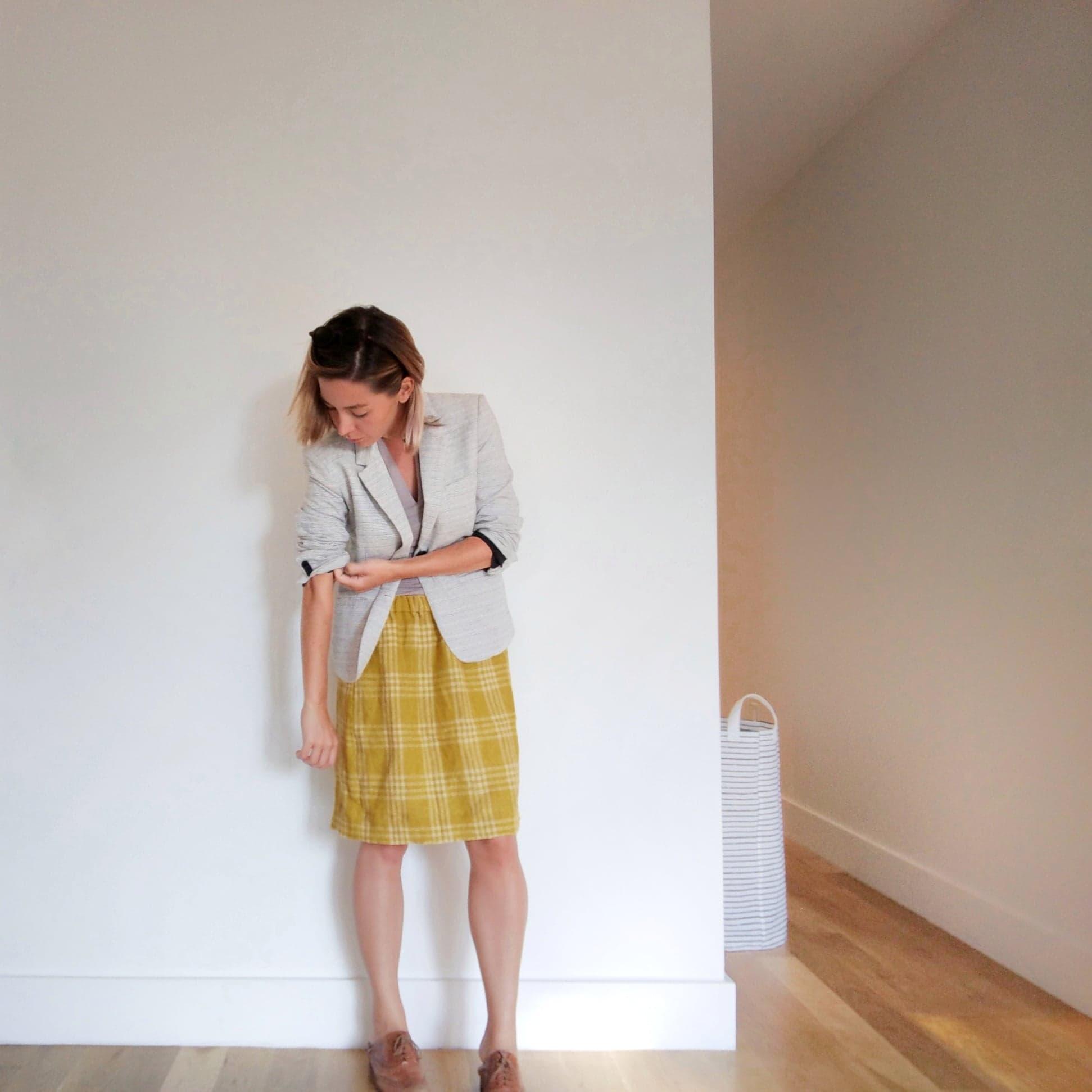 leanne wearing a gray blazer, lavender top, and mustard yellow linen plaid skirt with tan leather shoes