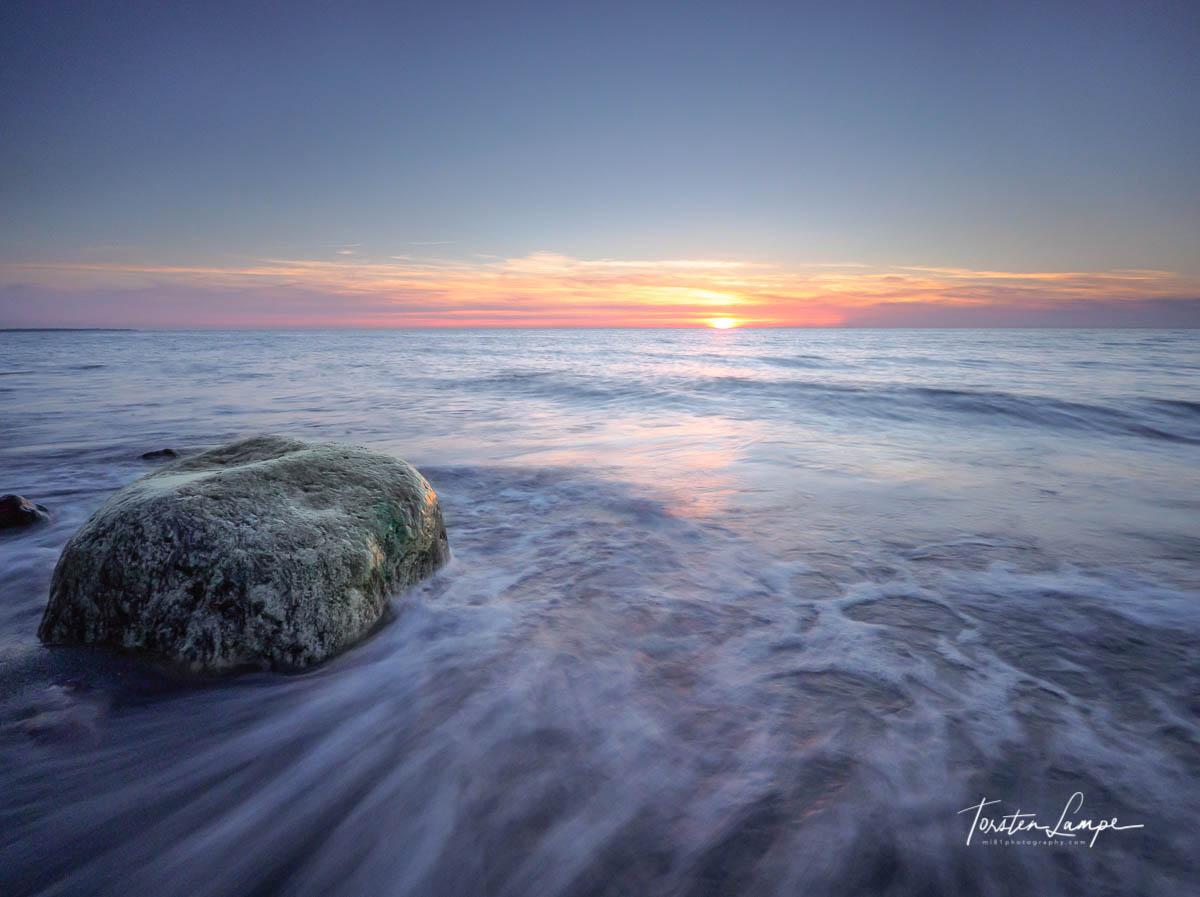 Rock in sunset breakers