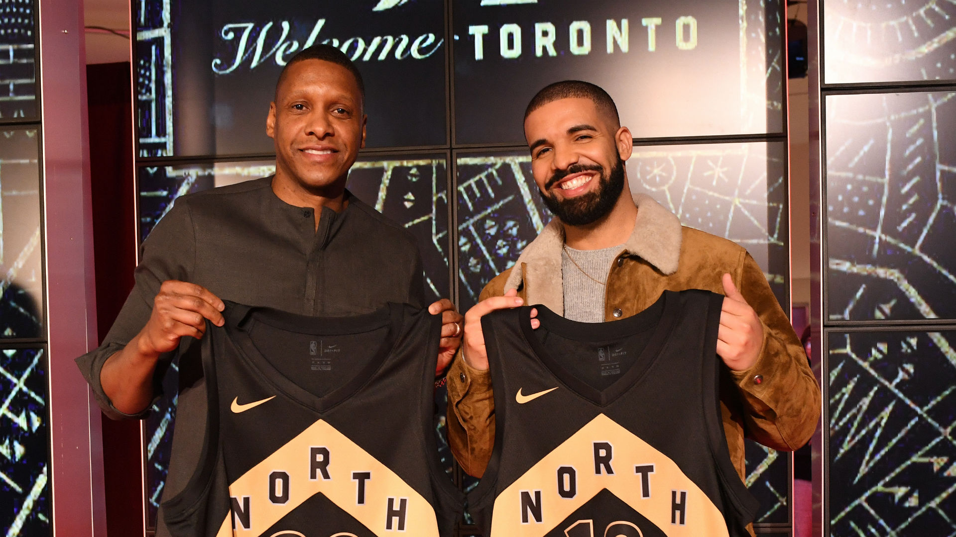 "Toronto Raptors Global Ambassador Drake and General Manager Masai Ujiri reveil the Toronto Raptors OVO uniforms they will wear in ""Welcome Toronto"" home games. (Photo by The Score)"