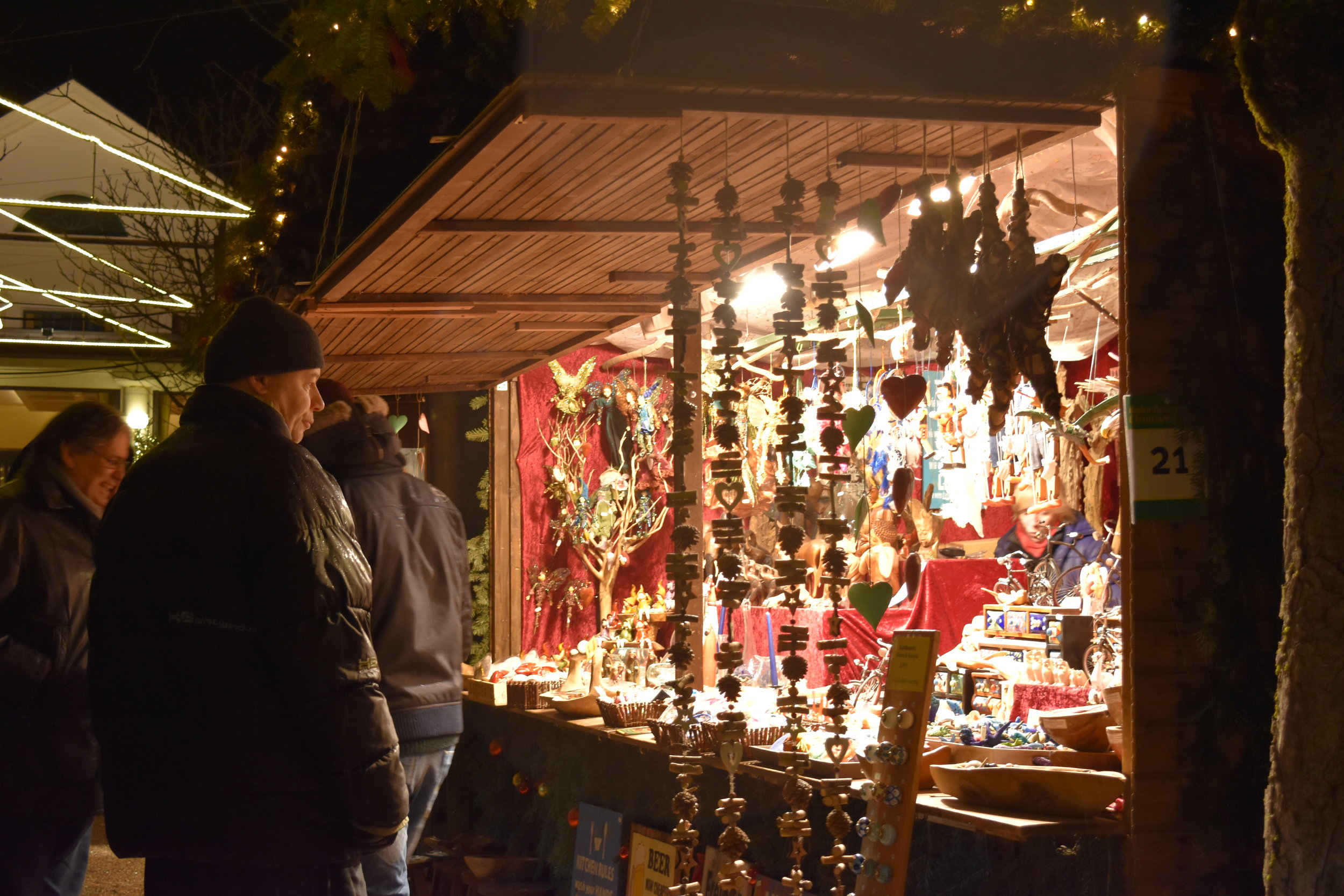 An onlooker is admiring the trinkets in the booth at the Christmas Market in Baden Baden, Germany.