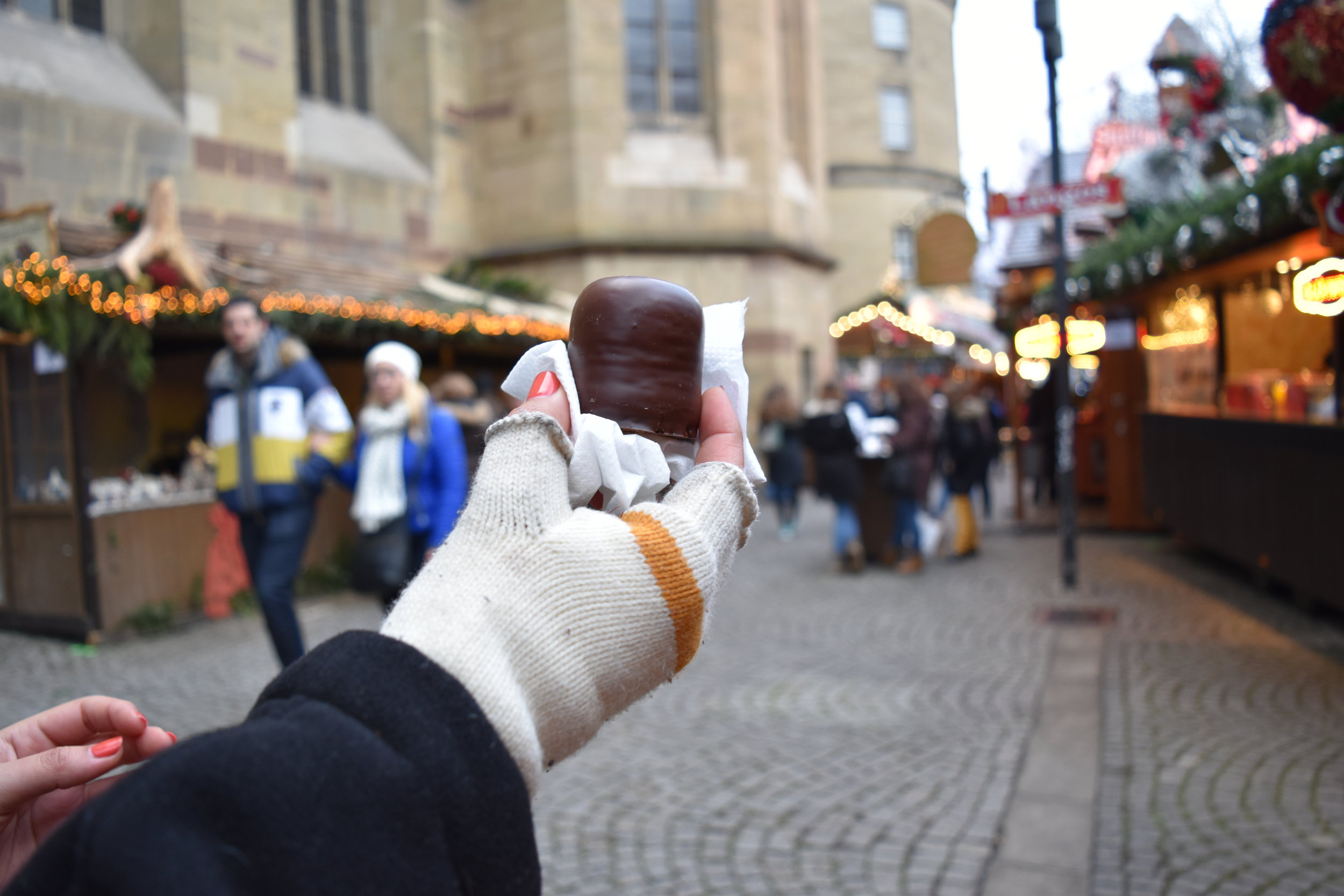 Patrons enjoy sweet treats such as Schokokuss (chocolate covered marshmallows) at the Christmas Market in Stuttgart, Germany.