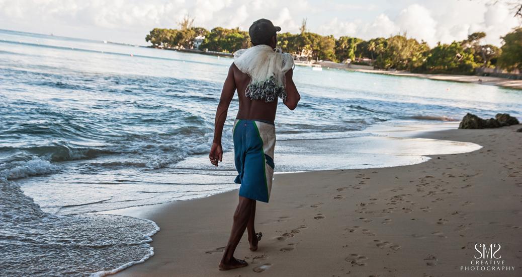Fisherman walking along Barbados beach1