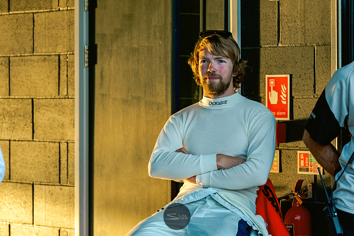 The afternoon sun creeping through the open garage doors at Silverstone Circuit, creating a golden light on racing driver Michael Lyons.