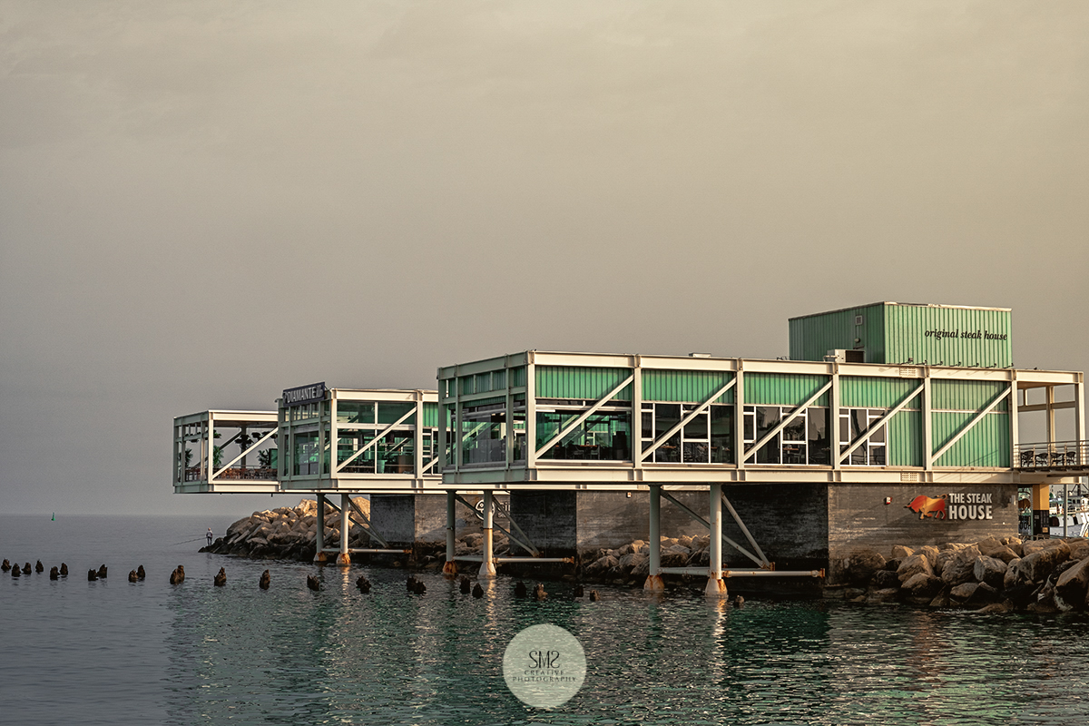 The cold and cloudy light just before the 'golden hour' falling on this restaurant at Larnaca Marina, Cyprus.