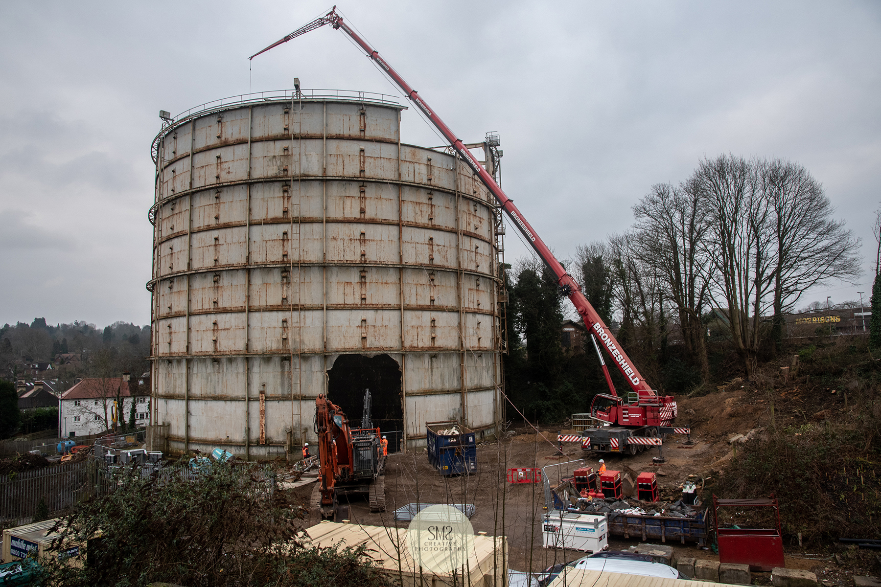 A piece from the side of the gas holder removed so the crane has access to the furthest part of the roof to complete the top removal