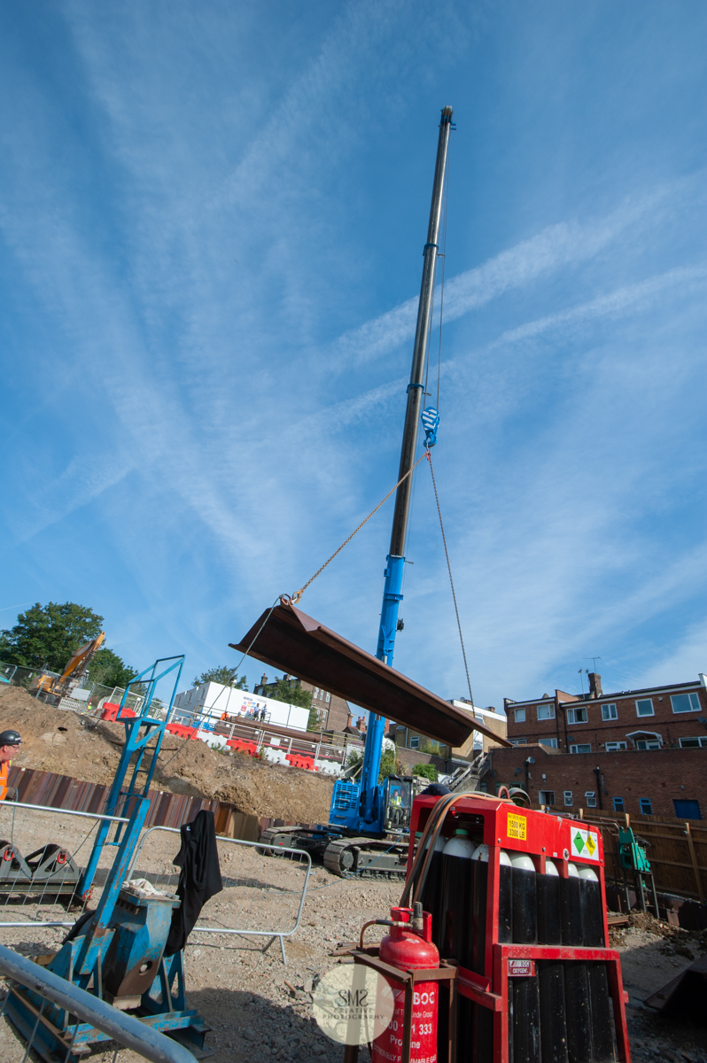 A view of the crane unloading the sheet piling from the delivery lorry on site