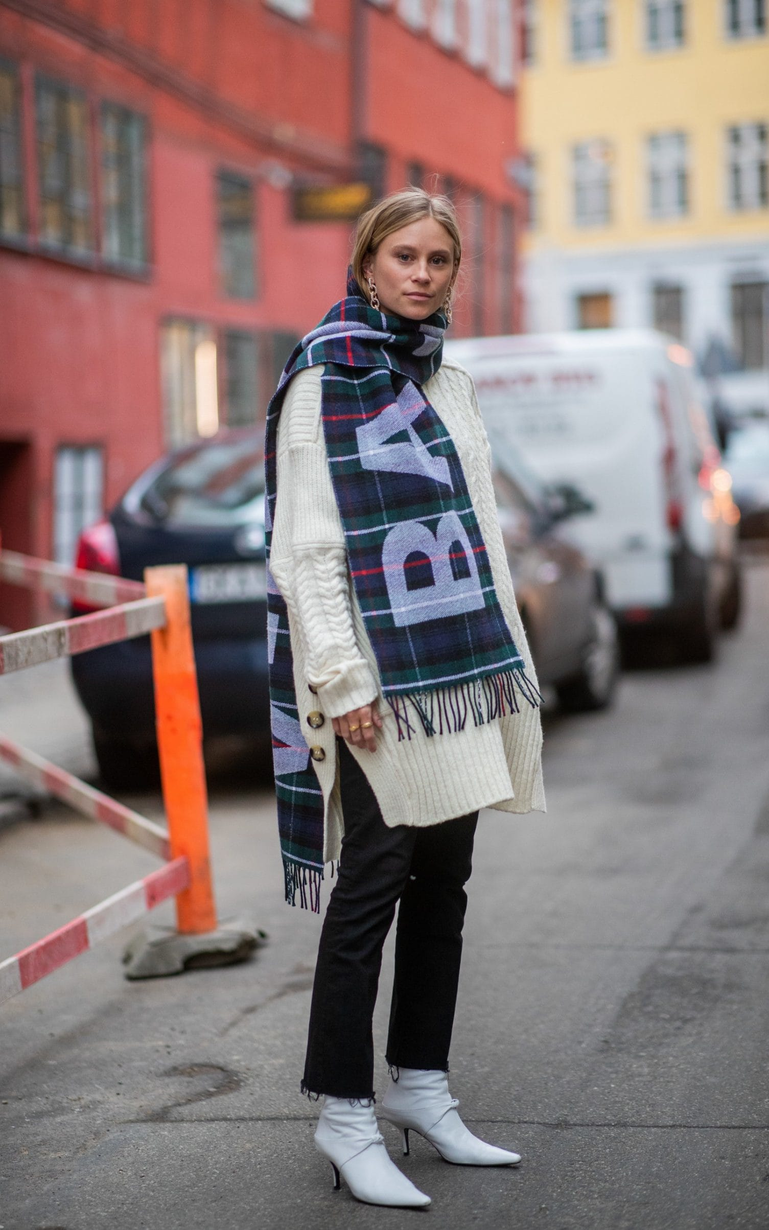 Tine Andrea looks effortlessly chic in her oversize knit, jeans and white boots but adds a bit of va va voom with the Balenciaga scarf.