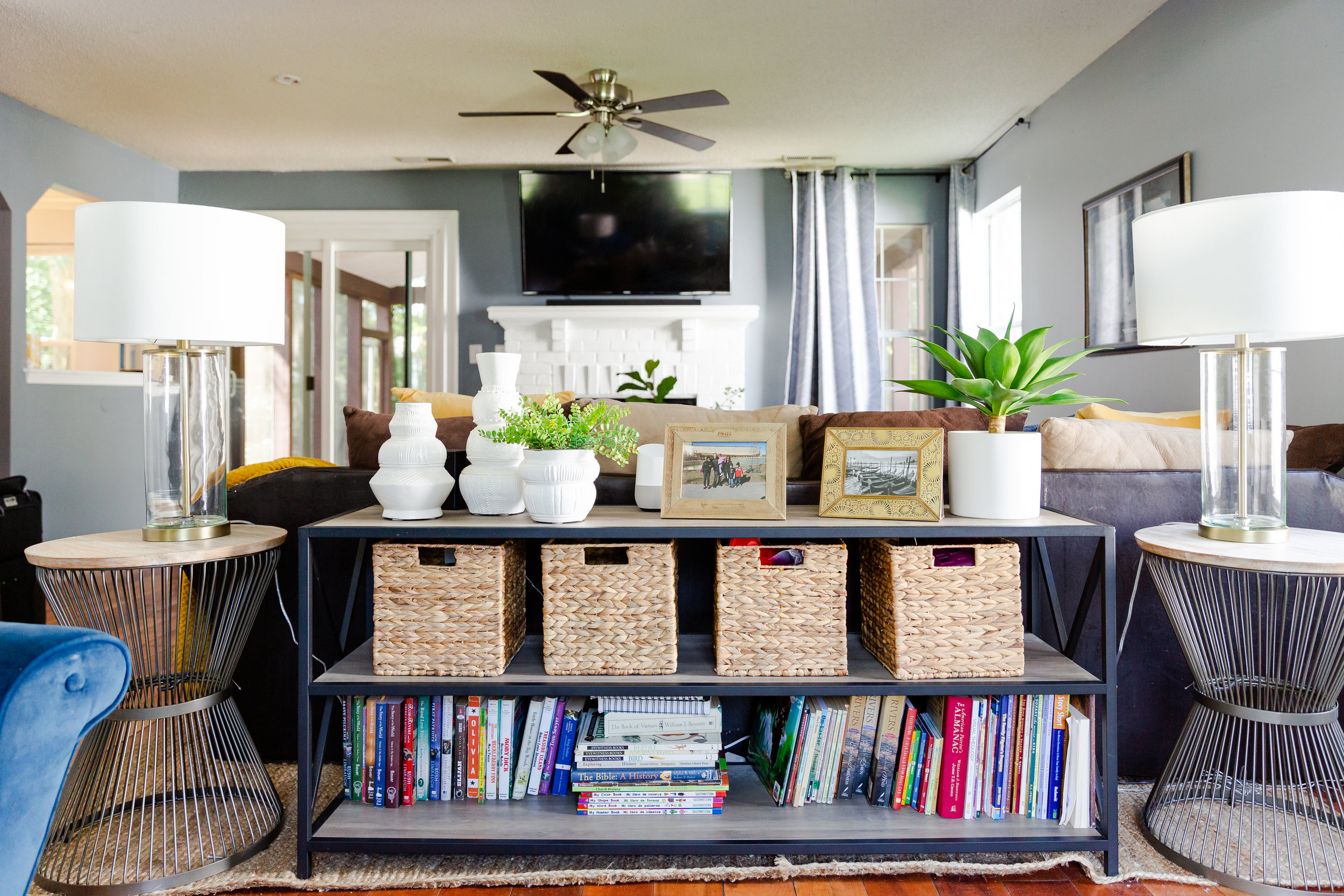 We added some storage back into the living room for books and toys, with this wooden and metal shelf.  It fits perfectly behind the Rivera's sectional, adding as a sort of divider.