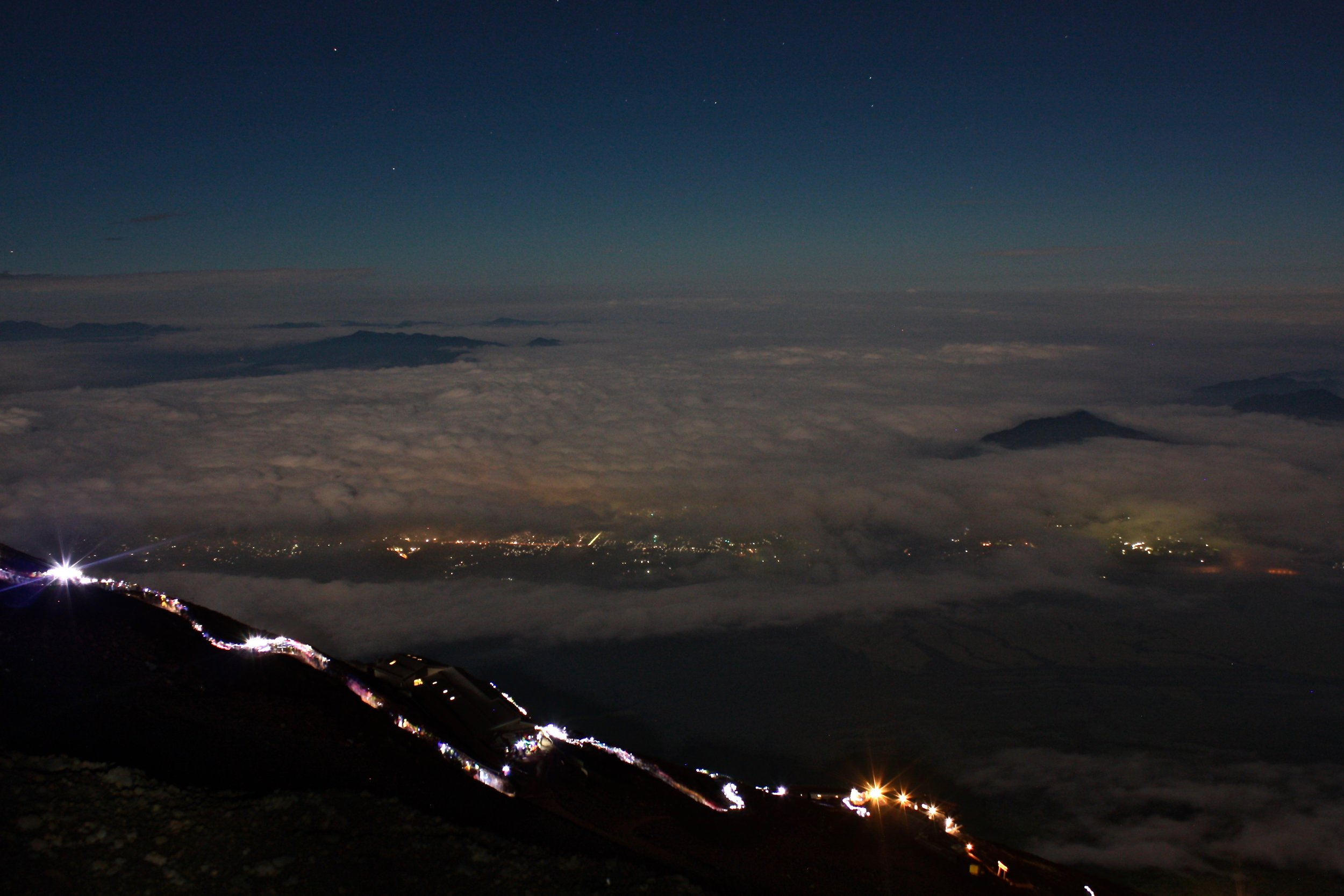 A trail of headlights makes their way up the mountain and a blanket of cloud over the city of Tokyo below.