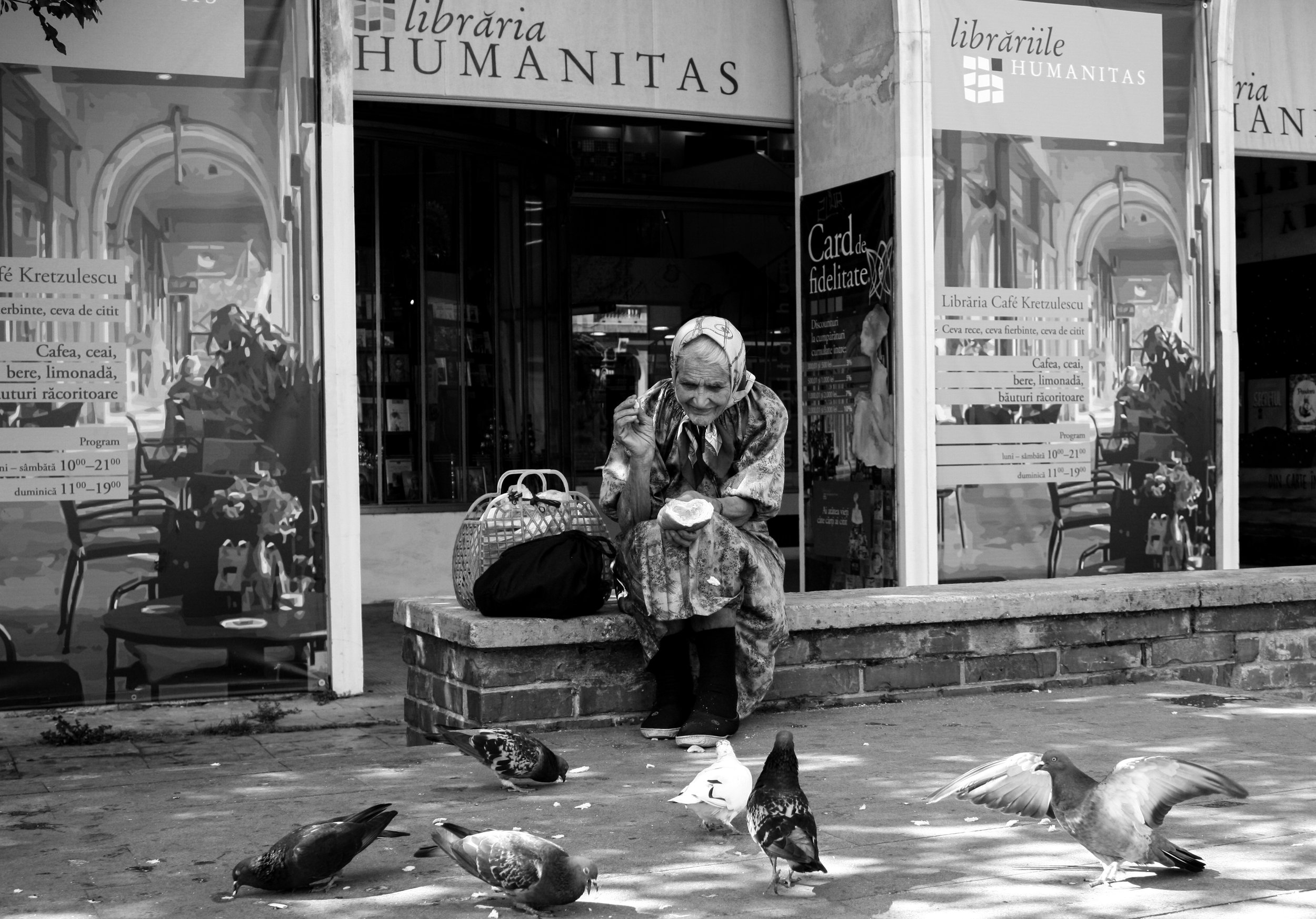 An old lady feeds pigeons outside Kretzulescu Church