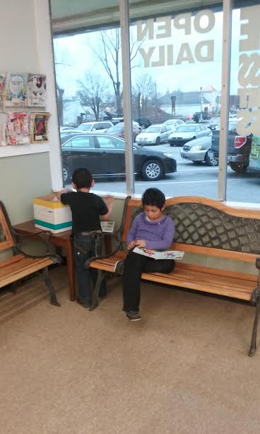 CHILDREN READING WHILE MOM DOES THE FAMILY LAUNDRY