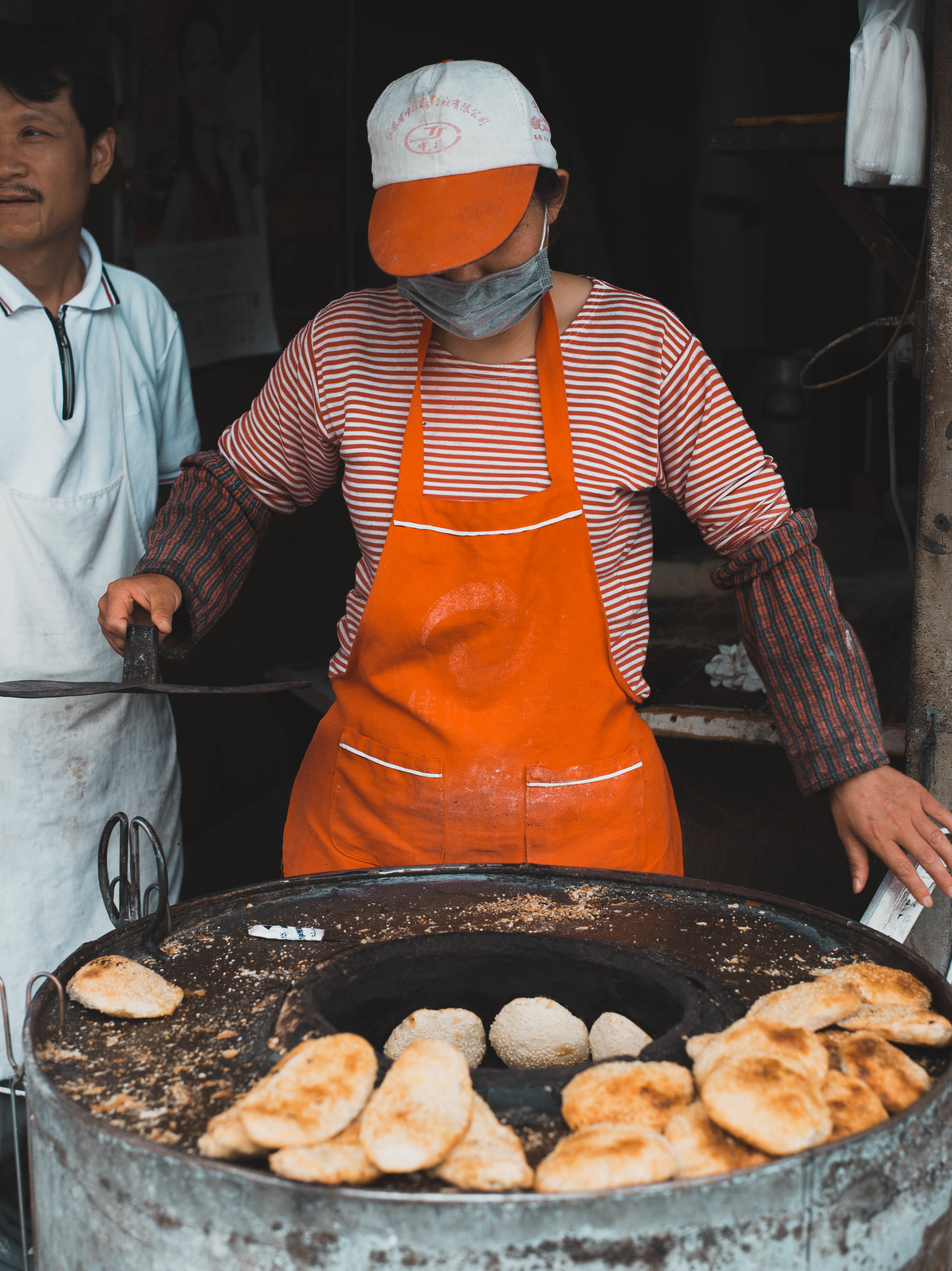 A local woman bakes Chinese biscuits in a large furnace