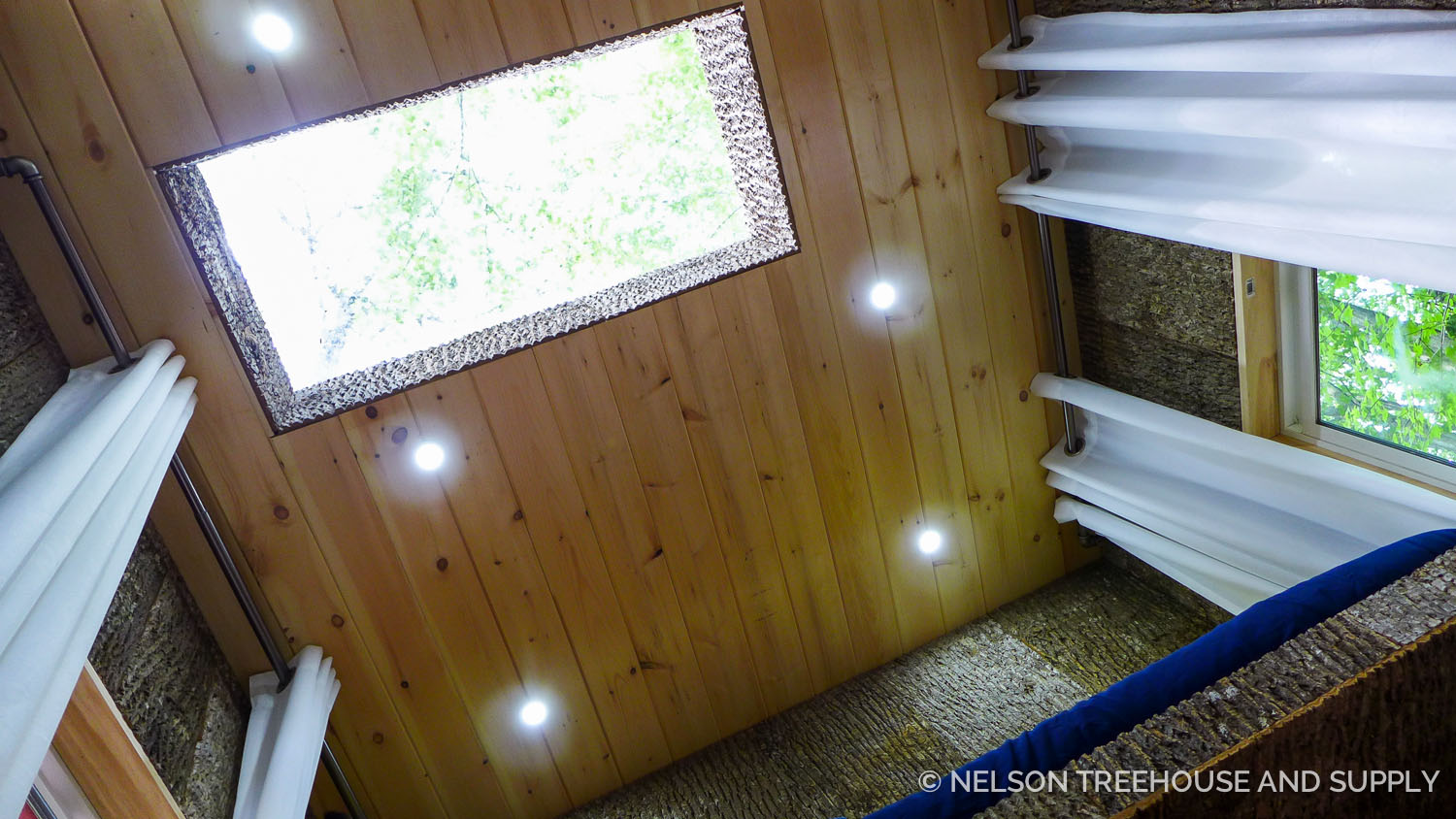 Bark paneling and a large skylight bring the outdoors inside the treehouse.