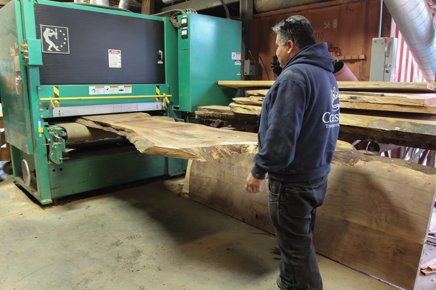 Ron Carlson, Sales partner at Wild Edge Woods and Owner of  Eaglehawk Enterprise , puts a slab through the sander.