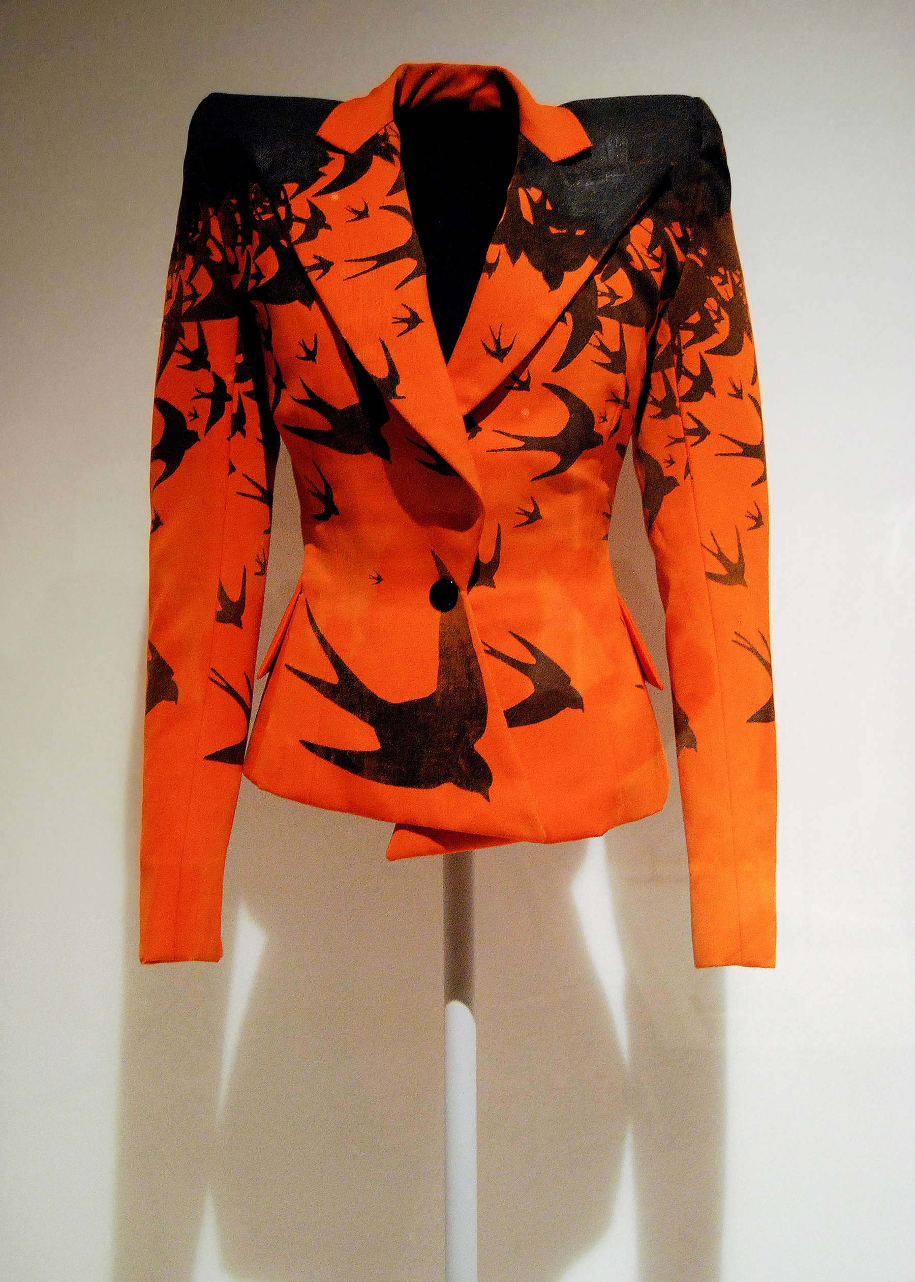 Alexander McQueen , Jacket, spring/summer 1995. Orange wool twill printed with black swallow motifs and hand-painted with black pigment.