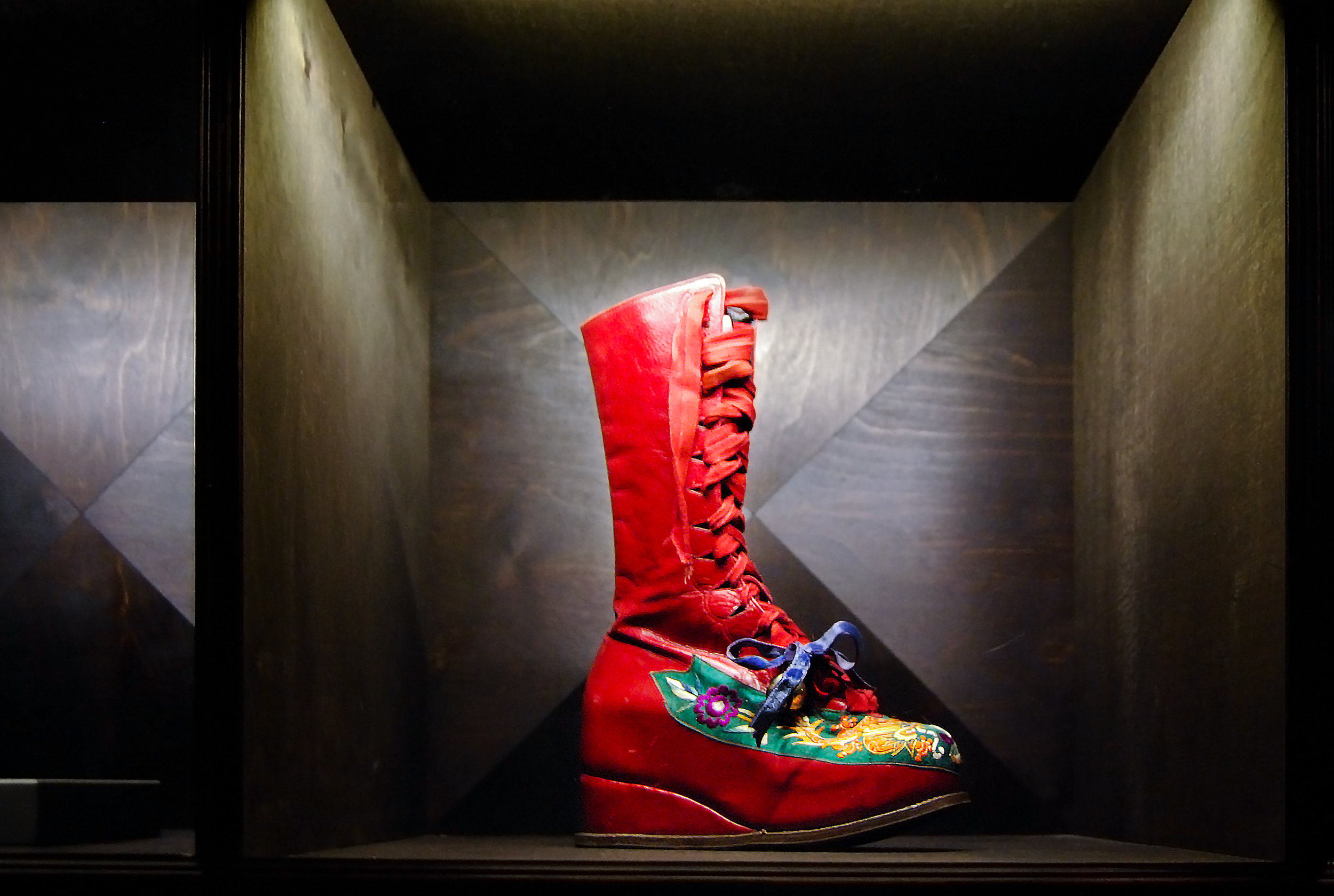 BACKGROUND PHOTO: Frida Kahlo's ornate red boot,which was once attached to her prosthetic right leg,on exhibit at  Museo Frida Kahlo . Photo © 2018  Arturo Veloira