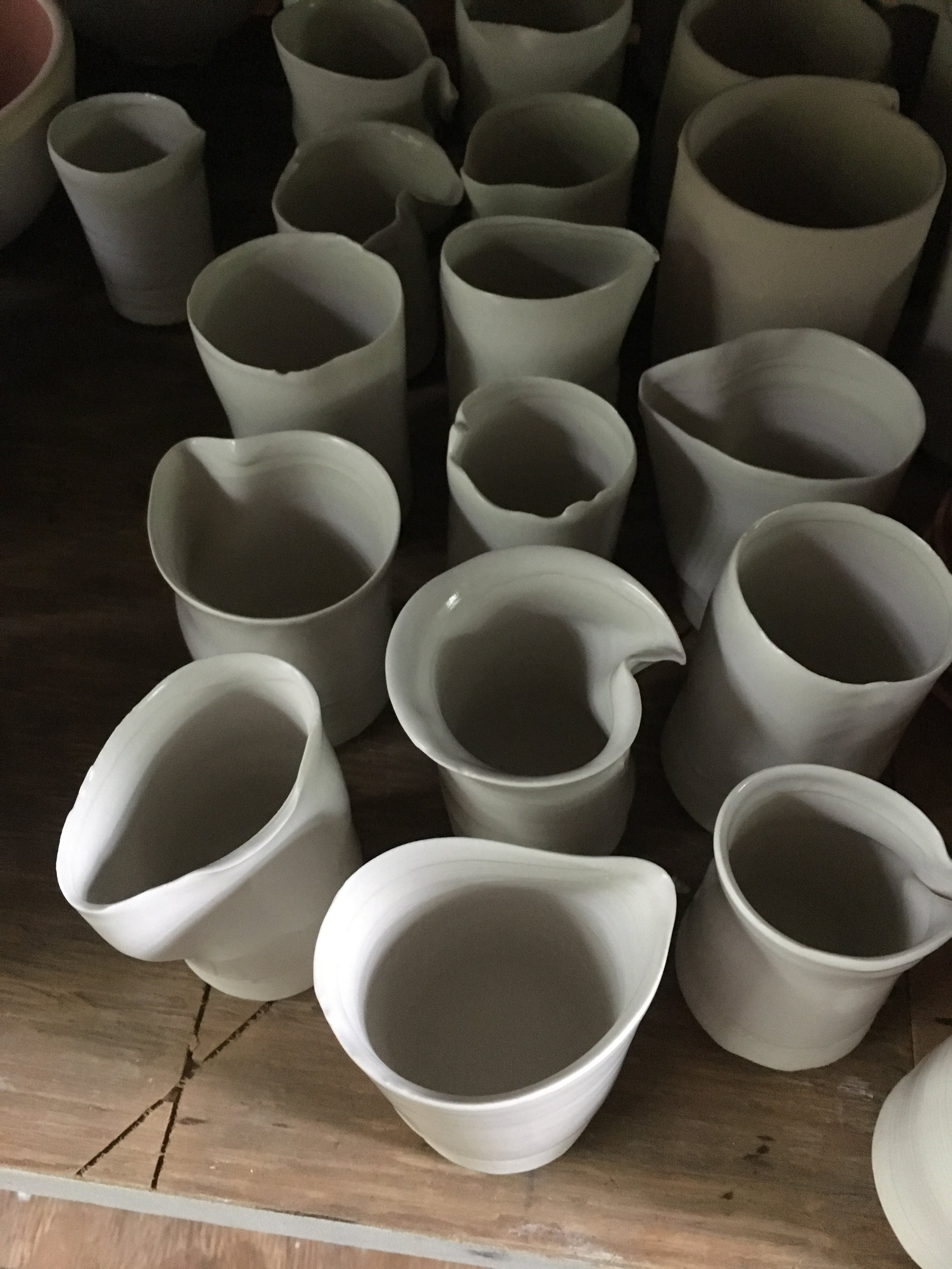 - This week I'm wood-firing 43 vessels for Plainsong Kico. They are glazed with Snow Cap Shino that fires as a mix of gray (in reduction) and white (in oxidation). Here are some of them lined up on the shelf in the kiln shed before the load-in.I'll post more pictures when I have my stoking shift on Thursday... And then pictures of the results at the July 1st kiln unloading!The firing lasts for three days, followed by a week-long long cool-down.May fire god Agni be kind to us.UPDATE: I got less ash and carbon trapping/ graying of the Shino than I hoped for, so the vessels are very subtle/ less tortured than last time. Also, everything that I fired as bisqueware shattered. The pieces that had already been fired to ^10, unglazed in the electric kiln, were fine.Images (left to right): my stoking shift - the first