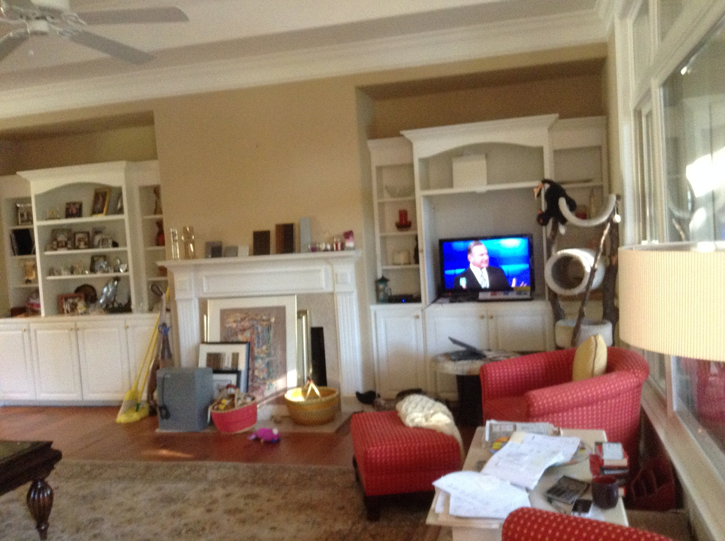 BEFORE: A traditional living space with white bookshelves framing the fireplace becomes...