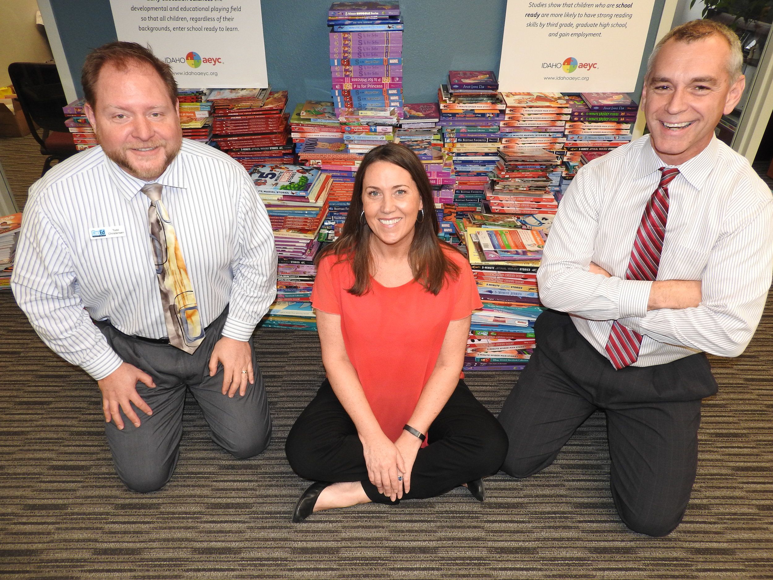 Beth Oppenheimer, Idaho AEYC, with Todd Erickson (R) and Todd Christensen (L), CapEd Credit Union in front of the 1,700+ donated books.