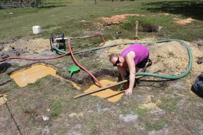Amy making sure the water hose doesn't clog with mud