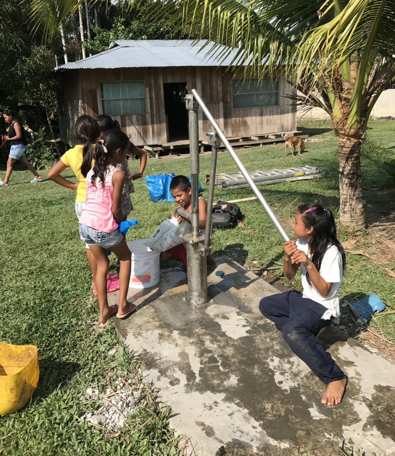 Children enjoy the water of a repaired well in the Amazon