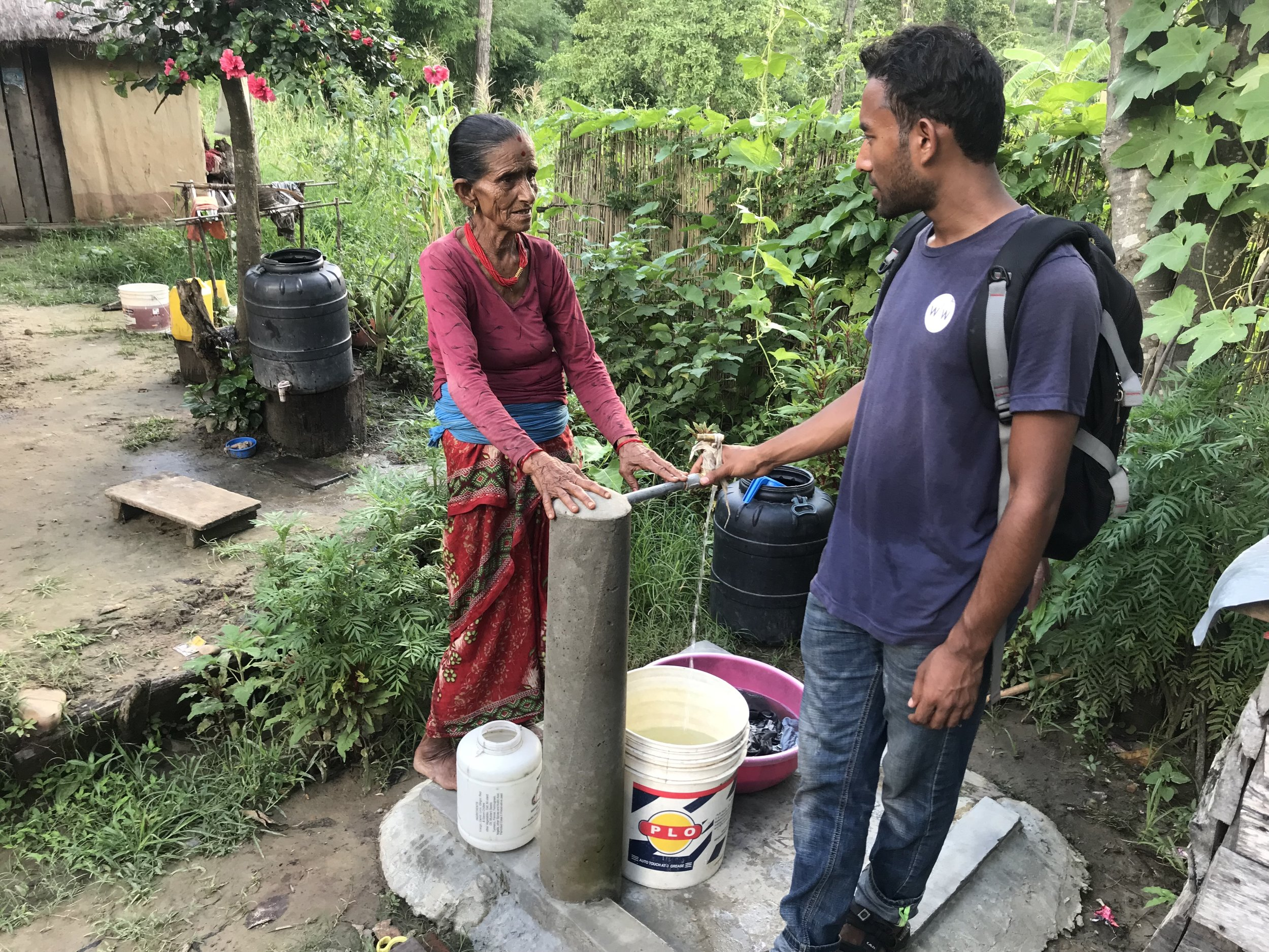 Nepal Field Coordinator Abhishek Basnet speaks with a woman about her community's new tapstand.