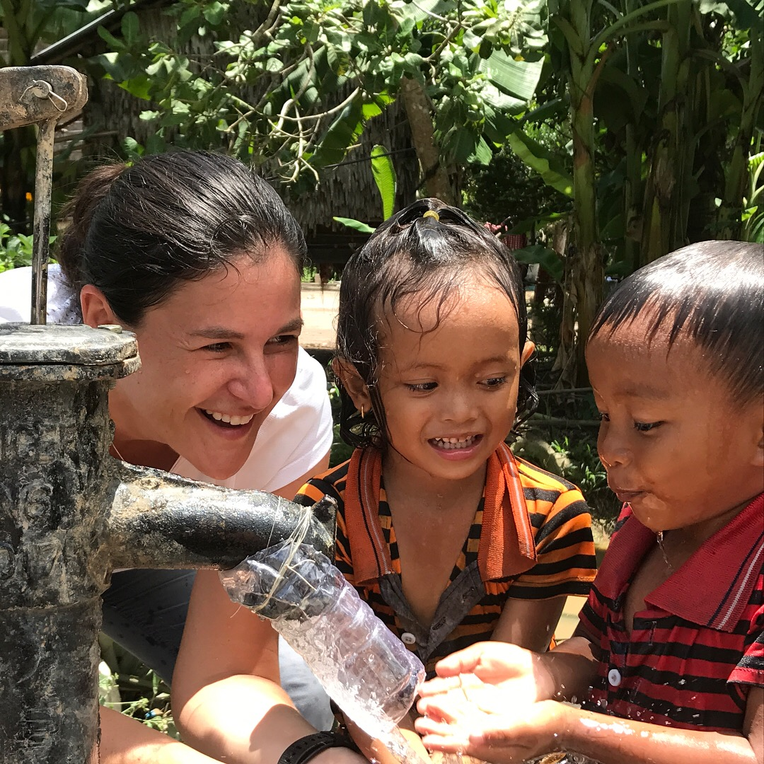 W|W Volunteer Program Director, Lisa Merritt, teaches young children how to use their new hand-pump well.