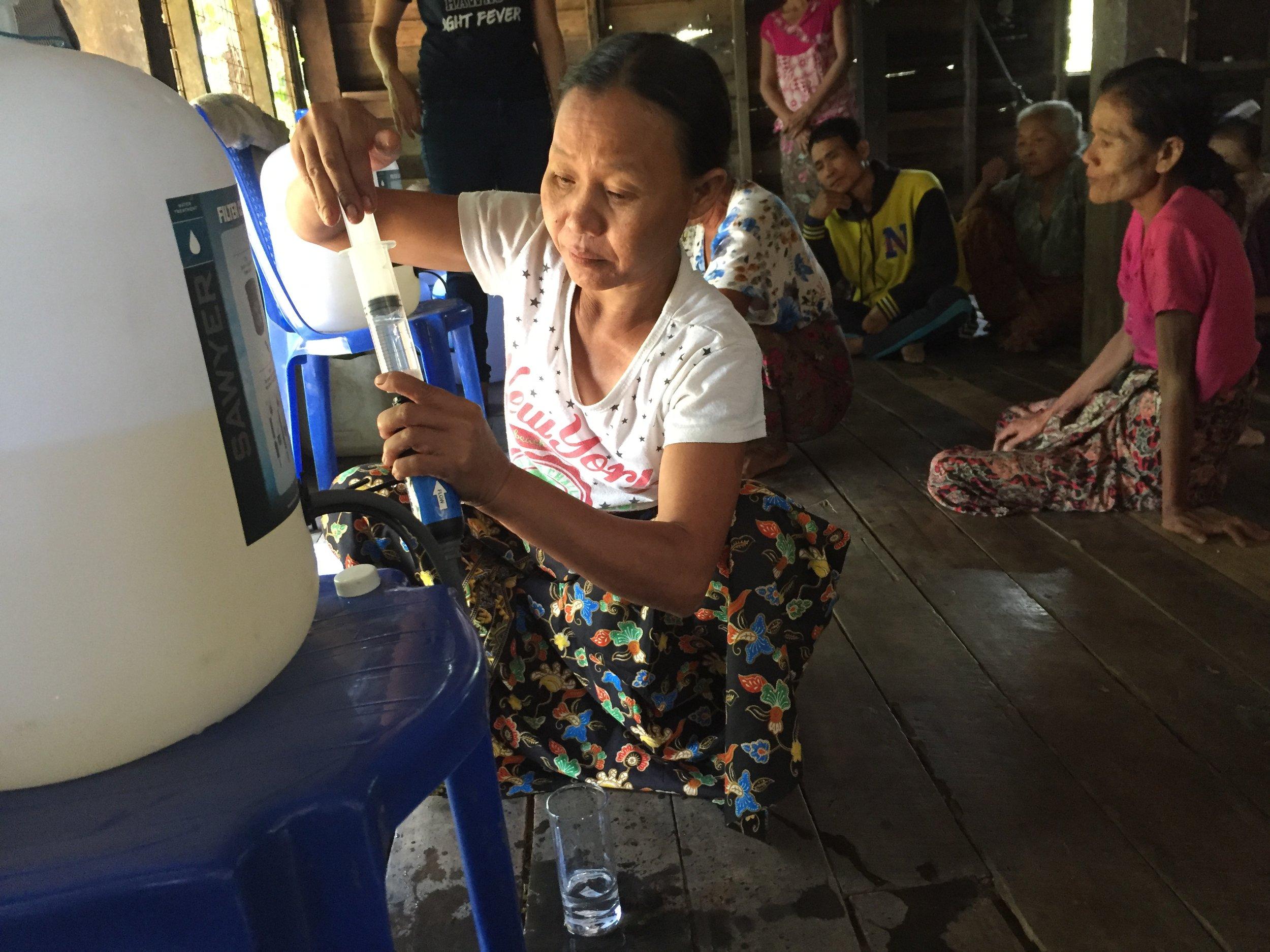 Community member demonstrating how to back flush the filter.
