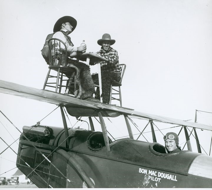 """Two wing walkers sit at table on the wing of Jenny airplane… ready to say """"cheers!"""" at a high altitude!"""
