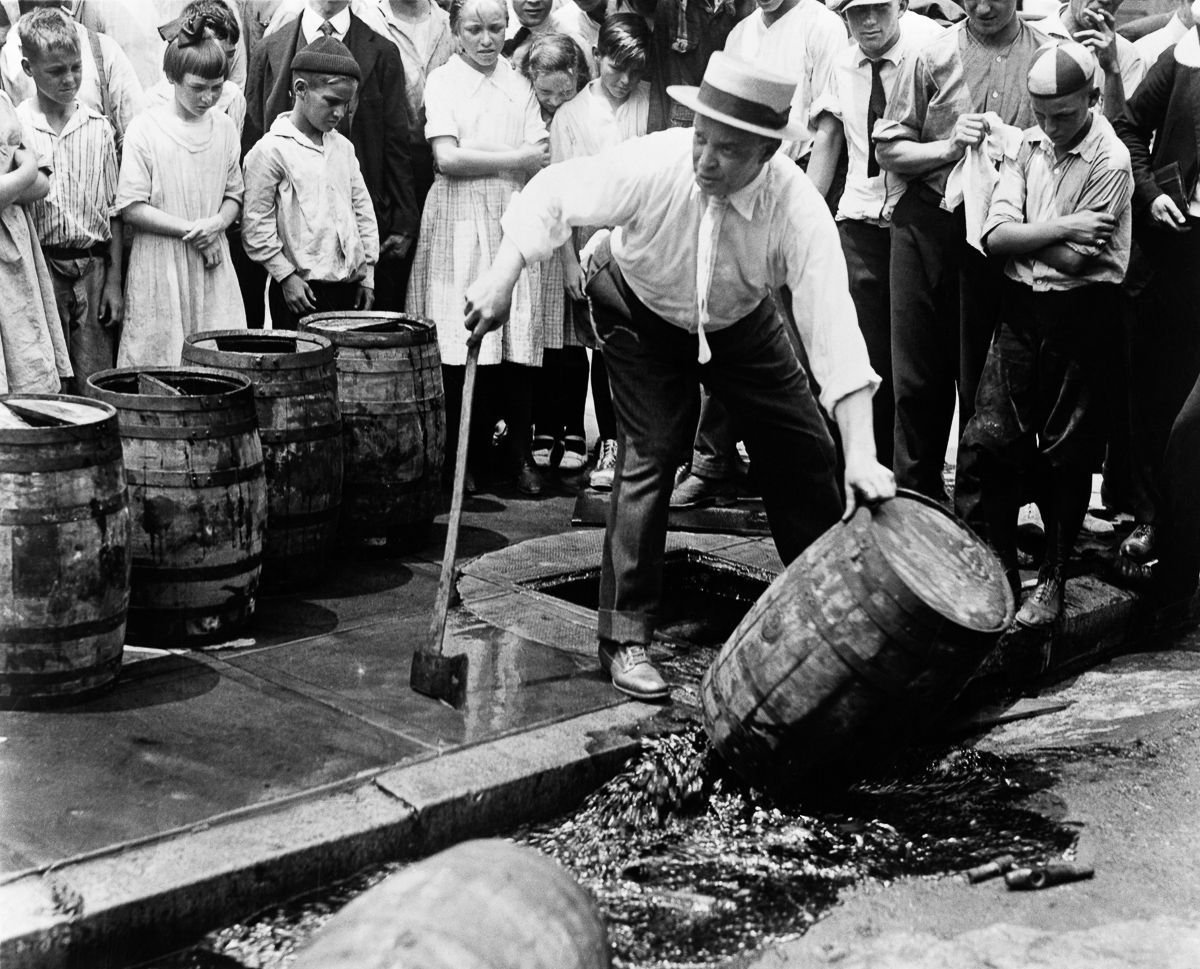 1920, a policeman empties a barrel full of liquor in public. Alcohol is officially banned.