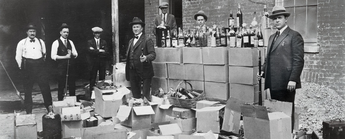Federal Prohibition Bureau confiscating illegal liquors at a speakeasy.