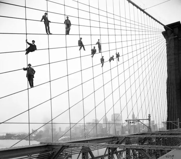 In this Oct. 7, 1914, photo provided by the New York City Municipal Archives, painters are suspended from wires on the Brooklyn Bridge in New York.