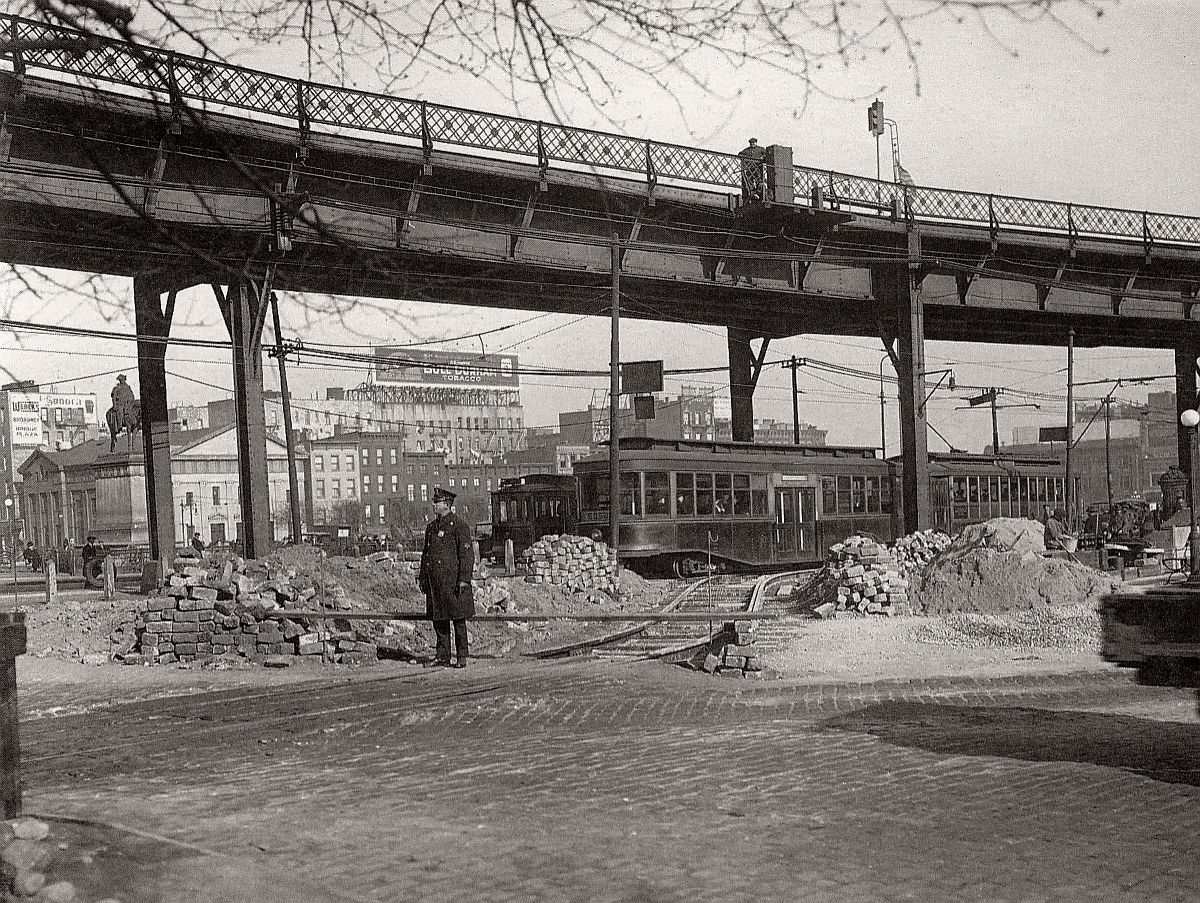 A lone policeman guards the end of the trolley line on Roebling Street at the Williamsburg Bridge plaza. A stack of cobblestones and a man rolling a new tire behind him. Brooklyn. 1921