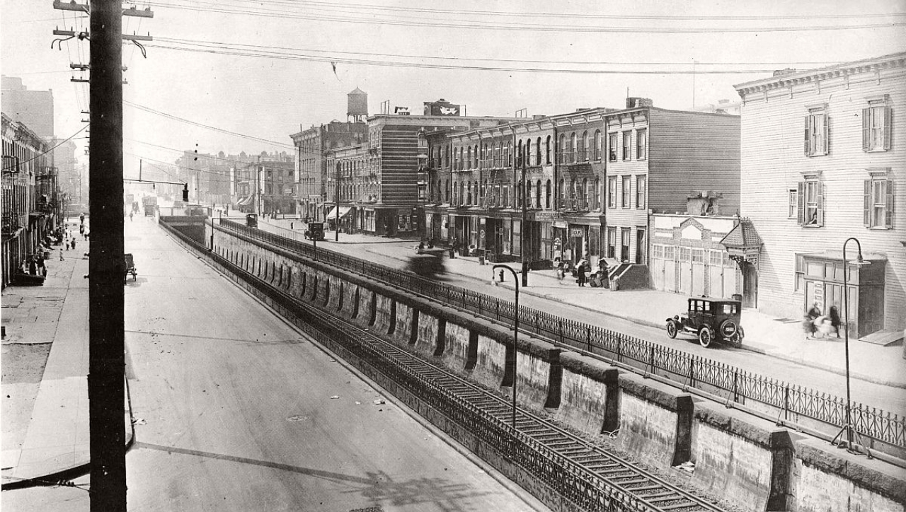 Atlantic Ave looking west from the Sackman St bridge. Long Island Railroad emerging from a tunnel. New 1920s cars zoom along as kids play on the sidewalk. Brooklyn, 1923