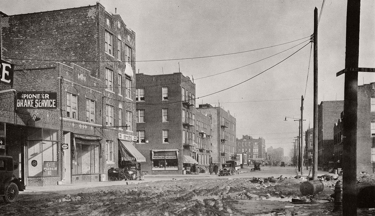 Brand new 4 floor brick apartments, car heaters for $10, unpaved muddy street, a lady with baby stroller. 1920s cars. Blake Ave from East 98th St toward Union St. Brooklyn, 1927