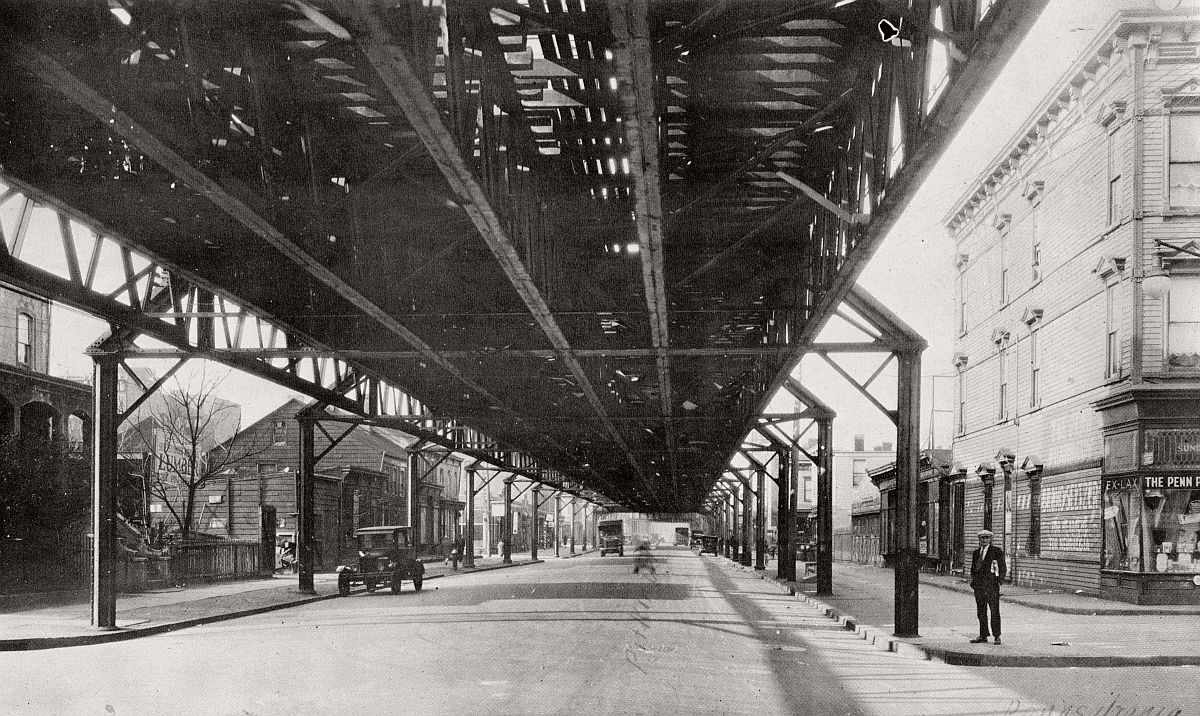 Man in a cap with today's newpaper, 1920s car parked, old wood frame house from the 1800s still there, Elevated railroad overhead. Pitkin Avenue looking west from Pennsylvania Avenue. Brooklyn. 1929